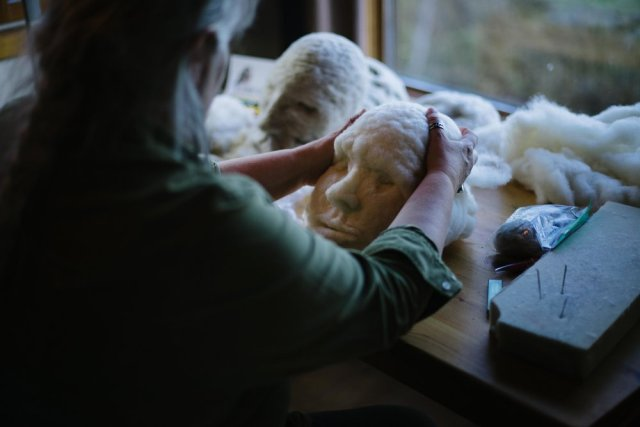 Artist Rosemarie Péloquin needle-felting a 3D face with white natural wool; sitting at a table in improvised studio at Falcon Trails Resort residency. photo: Emily Christie