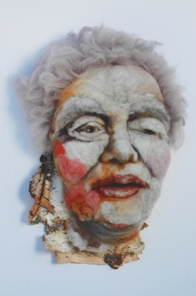 Marguerite - Hand needle-felted wool sculpture of a female face with wispy purple hair. Mounted on reclaimed birch bark. Artist/photo: Rosemarie Péloquin.
