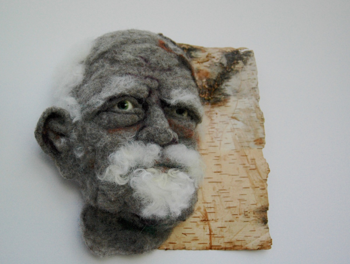Sortons des bois - Hand needle-felted wool sculpture of a male face – balding with wispy white hair and goatie. Mounted on reclaimed birch bark. Artist/photo: Rosemarie Péloquin