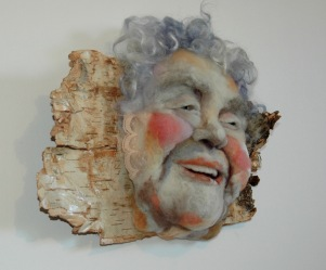 Rose Alba - Hand needle-felted wool sculpture of a female face – laughing, blue haired. Mounted on reclaimed birch bark. artist/photo: Rosemarie Péloquin.
