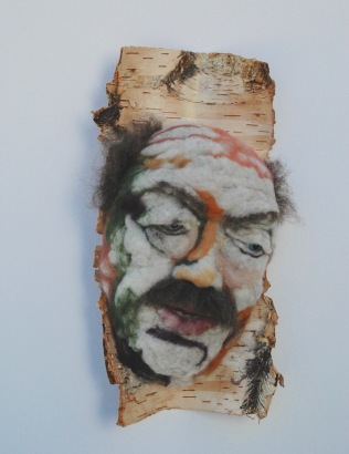 Télesphore - Hand needle-felted wool sculpture of a male face, balding with bushy brown moustache. Mounted on reclaimed birch bark. Artist/photo: Rosemarie Péloquin.
