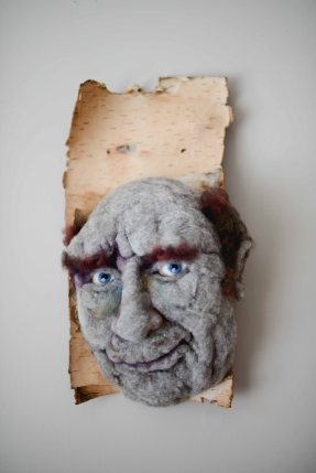 Hugo - Hand needle-felted wool sculpture of a male face – baldish with a slight grin. Mounted on reclaimed birch bark. artist: Rosemarie Péloquin; photo: Emily Christie.