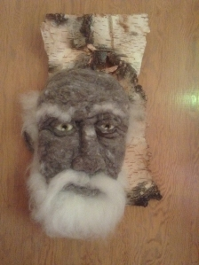 Marcus - Hand needle-felted wool sculpture of a male face with green eyes and wispy white beard and eyebrows. Mounted on reclaimed birch bark. Artist/photo: Rosemarie Péloquin.