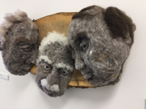 The Meeting 2016 - Hand-needlefelted wool sculpture - three male faces leaning together and looking out towards someone; mounted on cottonwood. artist: Rosemarie Péloquin. photo: Anne Fallis