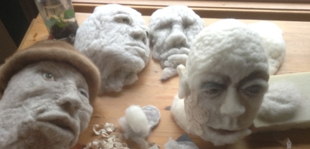 Four different wool heads in various stages of creation on artist Rosemarie Péloquin's work table.