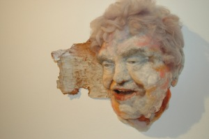 Mirth - Hand needle-felted wool sculpture of a female face – kind, chuckling. Mounted on reclaimed birch bark. artist: Rosemarie Péloquin; photo: Emily Christie.