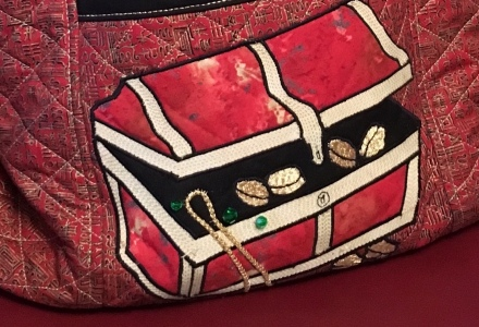 A cropped photo of a quilted treasure chest bag.