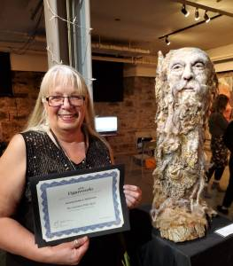 Rosemarie Péloquin standing with her certificate beside her winning sculpture.